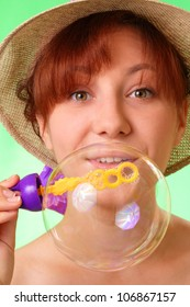 Pretty young girl in a hat blowing soap bubbles