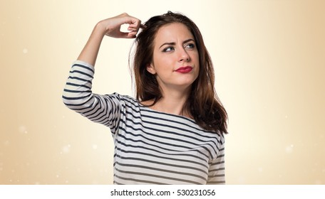 Pretty young girl having doubts on ocher background