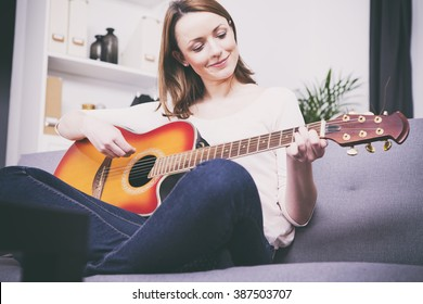 Pretty young girl having her legs crossed playing some record on guitar sitting on couch