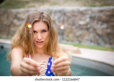 Pretty young girl having Sparkler fun in the pool celebrating the 4th of July