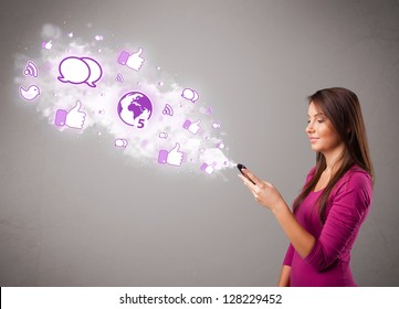 Pretty young girl holding a phone with social media icons in abstract cloud