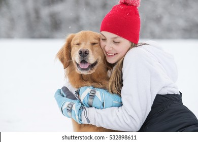 Pretty young girl hugging her golden retriever dog in the snow