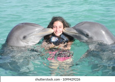 pretty young girl kiss by two dolphins in pool sea
