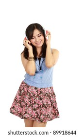 pretty young girl listening music with her headphone. in isolated over white