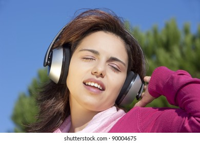 Pretty young girl listening music in the park
