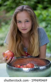 Pretty young girl with long blond hair sitting at a table in the garden with a bowl of fresh apples holding one in her hand for a healthy summer snack