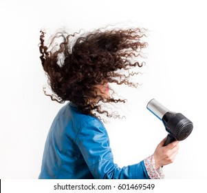 Pretty young girl with long curly hair holding hairdryer. Movement of beautiful curls