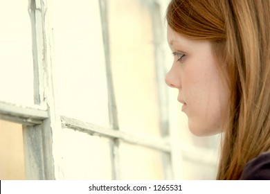 pretty young girl looking through some old broken windows