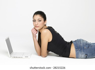Pretty young girl lying on floor with laptop