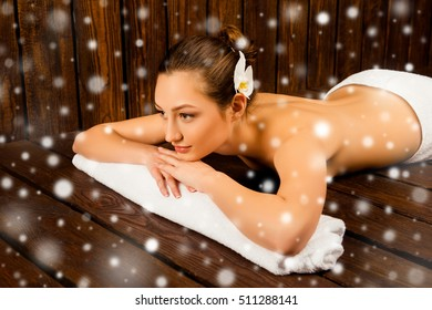Pretty young girl lying in sauna and relaxing, xmas concept
