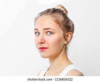 Pretty young girl with make-up and blue eyes poses in studio, close up portrait