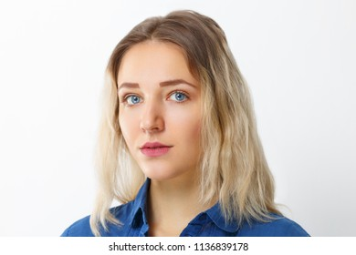 Pretty young girl  with make-up in blue shirt poses in studio