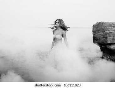 Pretty young girl in the morning sea, black and white