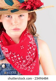 Pretty young girl in overalls with hat and bandana