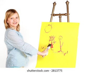 Pretty young girl painting on an antique easel