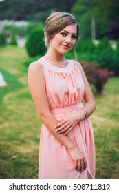 Pretty young girl with in a park with flowers in hand, a bridesmaid in a pink maxi dress.