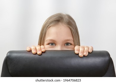 Pretty young girl peeking out from behind a black chair on white background.