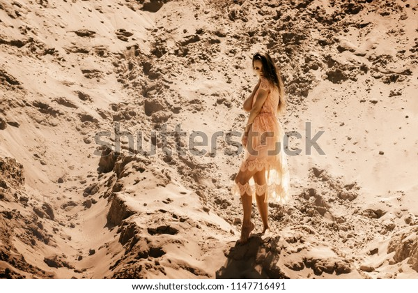 pretty young girl in pink dress looking at the camera in desert