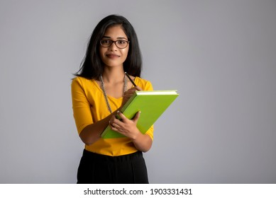 Pretty young girl posing with the book on grey background
