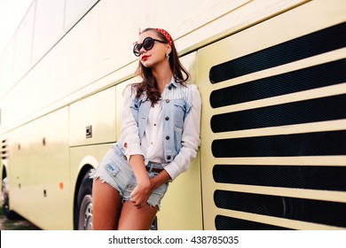 Pretty young girl posing near yellow bus in jeans shorts happy smiling in sunglasses with red lips having fun alone