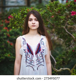 Pretty young girl posing with red flowers in greenhouse