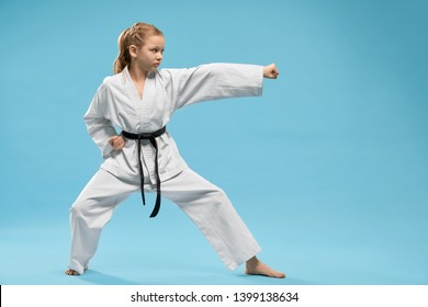 Pretty, young girl practicing karate and jujitsu. Confident junior wearing in white kimono with black belt standing in stance. Concept of wellness and martial arts.
