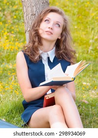 pretty young girl reading a book against a tree