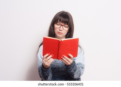 Pretty young girl with red book in glasses isolated
