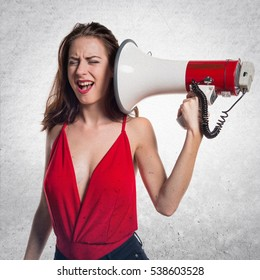 Pretty young girl shouting by megaphone on textured background