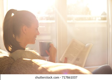 Pretty young girl sitting on sofa, drinking coffee and reading book. Cozy domestic atmosphere on beautiful sunshine