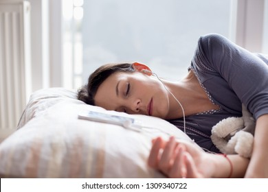 Pretty young girl sleeping in bed with earphones and mobile phone on pillow. Music for resting concept