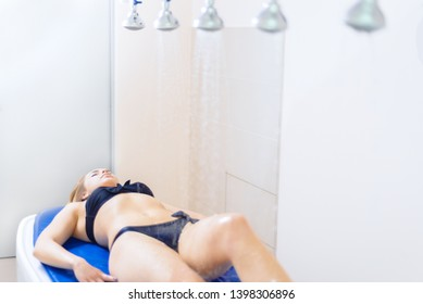 pretty young girl in swimsuit in the spa salon. a woman takes a Vichy shower. hydromassage. body care concept