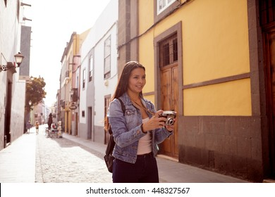 Pretty young girl taking pictures in a narrow paved street with old buildings wearing casual blue jeans and a denim jacket