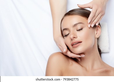 Pretty young girl with thick eyebrows and perfect skin doing facial massage, beauty photo concept, hands on face, skin care, closed eyes, close up.