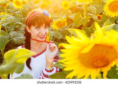 Pretty young girl in traditional ukrainian blouse embrodery looking to camera on a sunflower plant at sunset, backlight.