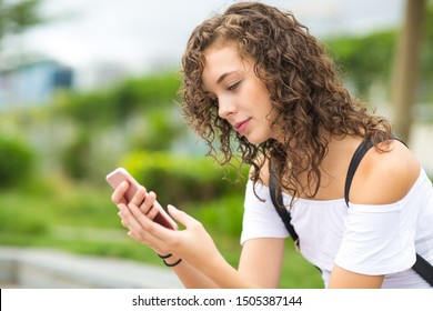 Pretty young girl using a mobile phone at the park.