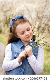Pretty young girl walking in the blossoming park