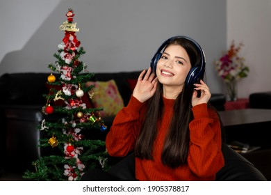 Pretty young girl wearing headphone and listening to music or songs with a smile on her face, raising hands, sitting next to a Christmas tree in her living room.
