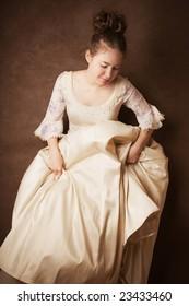 Pretty young girl in wedding dress on dark background