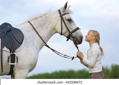 Pretty young girl with a white horse.