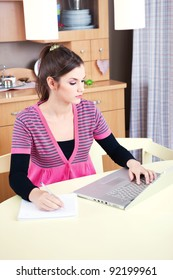 Pretty young girl working on laptop at home