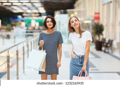 Pretty young girlfriends with paper bags standing in modern shopping center smiling at camera
