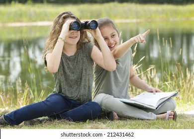 Pretty young girls exploring the environment with a binocular