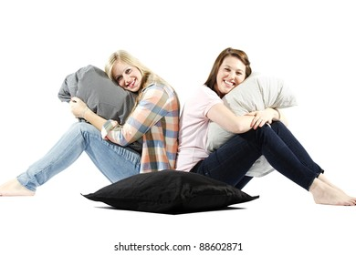Pretty young girls sitting back to back against white background