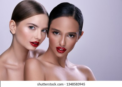 Pretty young girls wearing evening make up with naked shoulders posing at gray background, close up portrait.