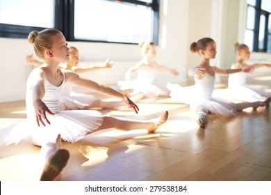 Pretty Young Girls, Wearing White Tutus, Sitting on the Floor at the Studio While Having a Training for Ballet Dance.