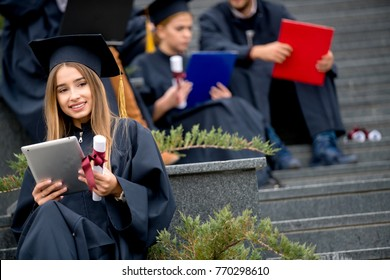 Pretty young graduate with collegues, teamwork, diploma