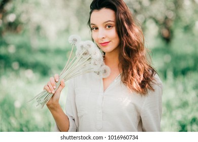 Pretty young happy brunette girl in white shirt with emotional cheerful face smiling, laughing like child in spring blooming garden with bouquet of dandelions. Cute female model posing at nature