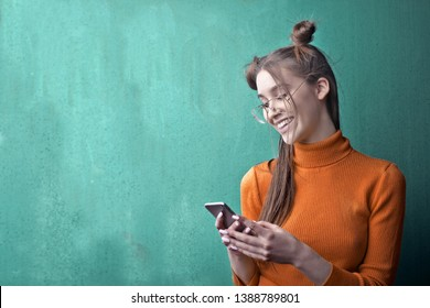 Pretty young happy girl texting on her smartphone.