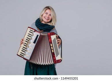 Pretty young happy woman with accordion. Playing music. Studio Shot. Over gray background